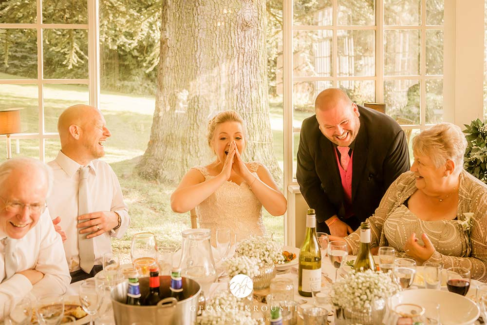 Derby wedding magician, Paul Grundle performing magic with bride and wedding party laughing in reaction to his trick