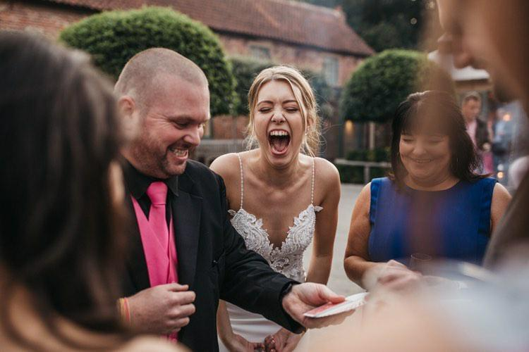 Derby Wedding Magician performing magic trick at Hazel Gap Barn in Nottingham whilst bride is laughing